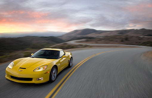 VET 01 RK0905 01 © Kimball Stock 2009 Chevrolet Corvette Z06 Yellow Driving On Highway At Dusk
