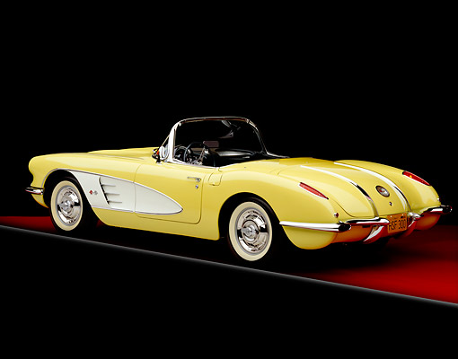 VET 02 RK0271 01 © Kimball Stock 1958 Chevrolet Corvette Convertible Yellow White Cove 3/4 Rear View On Red Floor Gray Line Studio