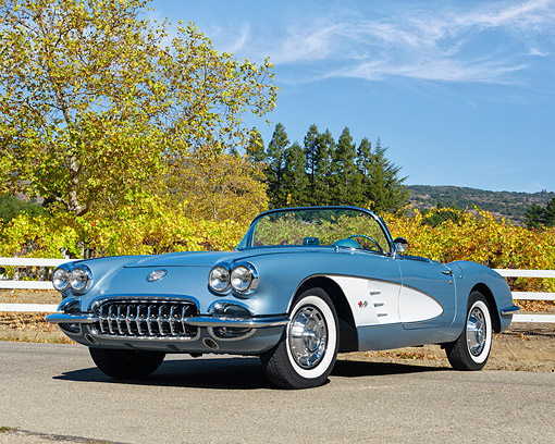 VET 02 RK0398 01 © Kimball Stock 1959 Chevrolet Corvette Convertible Frost Blue With White Cove 3/4 Front View On Pavement By Fence And Vineyard