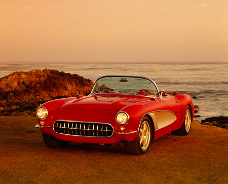 VET 02 RK0158 06 © Kimball Stock 1957 Chevy Corvette Custom Convertible Red/White 3/4 Front View On Sand By Ocean Headlights On Red Sky