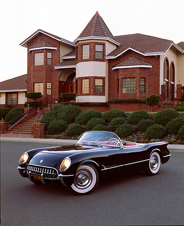 VET 02 RK0189 03 © Kimball Stock 1954 Chevrolet Corvette Convertible Black 3/4 Front View On Pavement By House