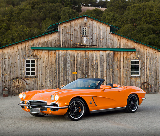 VET 03 RK0700 01 © Kimball Stock 1962 Chevrolet Corvette Convertible Orange 3/4 Front View On Pavement By Old Barn
