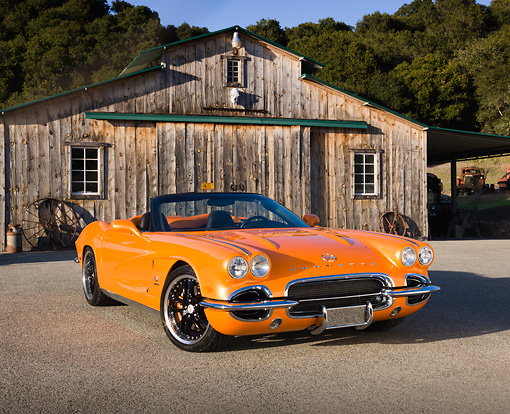 VET 03 RK0702 01 © Kimball Stock 1962 Chevrolet Corvette Convertible Orange 3/4 Front View On Pavement By Old Barn