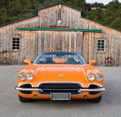 VET 03 RK0703 01 © Kimball Stock 1962 Chevrolet Corvette Convertible Orange Front View On Pavement By Old Barn
