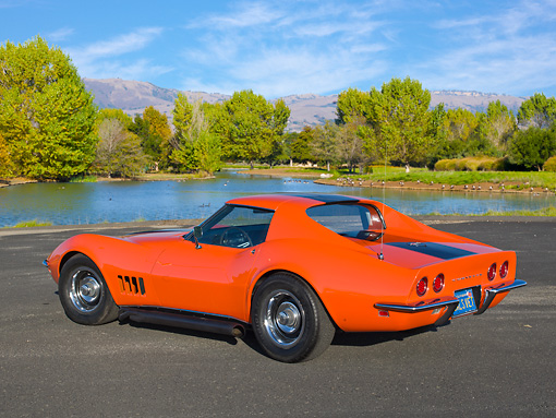 VET 03 RK0780 01 © Kimball Stock 1968 Chevrolet Corvette Orange With Black Stripe 3/4 Rear View On Pavement By Pond And Trees
