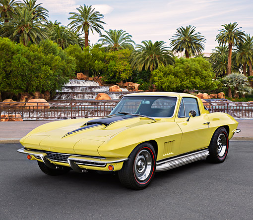 VET 03 RK0812 01 © Kimball Stock 1967 Chevrolet Corvette Coupe Yellow 3/4 Front View On Pavement By Fountain And Palm Trees