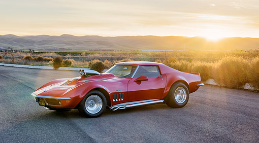 VET 03 RK0859 01 © Kimball Stock 1969 Chevrolet Corvette Stingray Red With Custom Graphics 3/4 Front View On Desert Road At Sunset