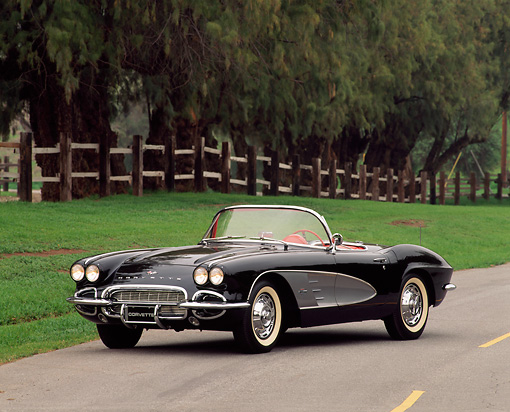 VET 03 RK0049 10 © Kimball Stock 1961 Chevrolet Corvette Convertible Black And Gray Front 3/4 View On Pavement By Trees And Fence