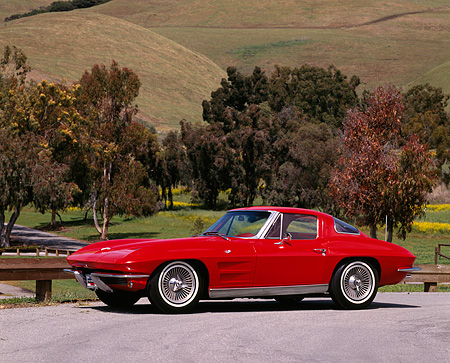 VET 03 RK0063 08 © Kimball Stock 1963 Chevrolet Corvette Split Window 327 Red 3/4 Front View On Pavement By Grass Hills And Trees