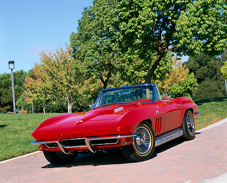 VET 03 RK0180 14 © Kimball Stock 1965 Chevrolet Corvette 396 Turbo Jet Convertible Red Front 3/4 View On Pavement By Trees