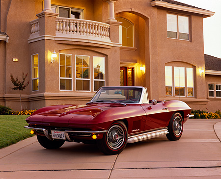 VET 03 RK0192 03 © Kimball Stock 1967 Chevrolet Corvette 327 Convertible Burgundy 3/4 Front View On Driveway By House Filtered