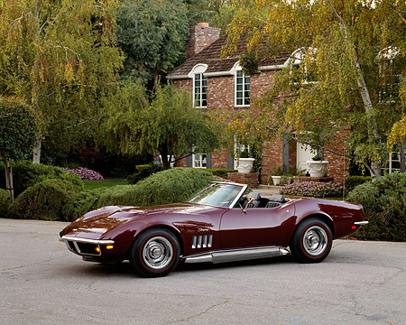 VET 03 RK0215 02 © Kimball Stock 1969 Chevrolet Corvette Stingray Convertible Burgundy 3/4 Side View On Pavement By House And Trees