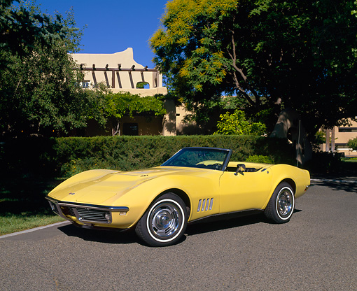 VET 03 RK0277 03 © Kimball Stock 1968 Chevrolet Corvette 427 Convertible Yellow 3/4 Front View On Pavement By Trees And Bushes