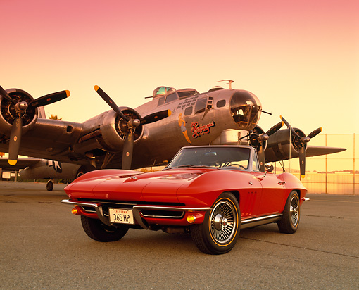 VET 03 RK0293 05 © Kimball Stock 1965 Chevrolet Corvette Convertible Red Low 3/4 Front View On Pavement By Plane Red Sky