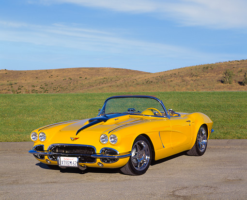 VET 03 RK0371 06 © Kimball Stock 1962 Extreme Chevrolet Corvette Convertible Yellow 3/4 Front View On Pavement By Grass Blue Sky