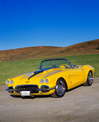 VET 03 RK0373 01 © Kimball Stock 1962 Extreme Chevrolet Corvette Convertible Yellow 3/4 Front View On Pavement By Grass Blue Sky