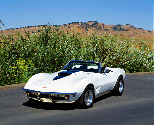 VET 03 RK0410 05 © Kimball Stock 1969 Chevrolet Corvette 427 Convertible White And Black Front 3/4 View On Pavement By Bushes