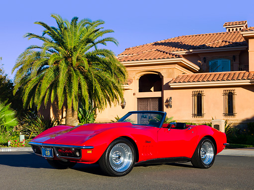 VET 03 RK0538 01 © Kimball Stock 1969 Chevrolet Corvette Stingray Convertible Red 3/4 Front View On Pavement By Palm Tree Building