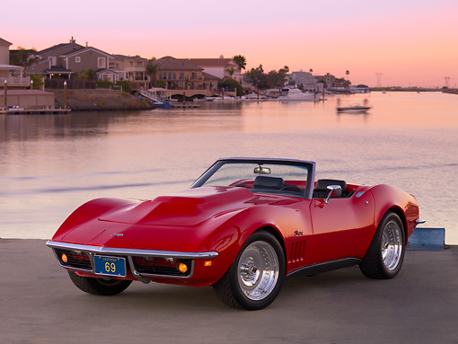 VET 03 RK0539 01 © Kimball Stock 1969 Chevrolet Corvette Stingray Convertible Red 3/4 Front View On Pavement By Canal And Homes