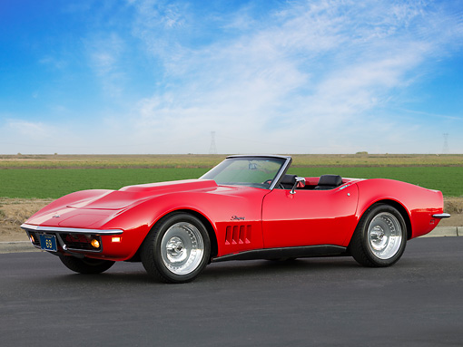 VET 03 RK0541 01 © Kimball Stock 1969 Chevrolet Corvette Stingray Convertible Red 3/4 Front View On Pavement By Field And Sky