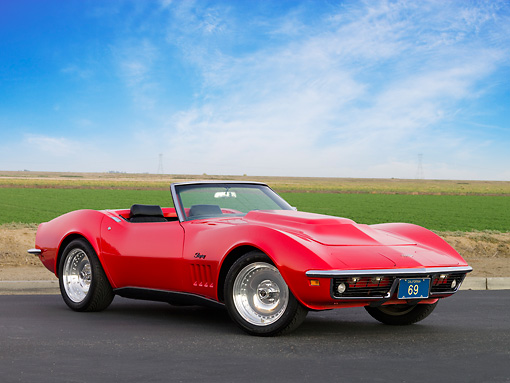 VET 03 RK0542 01 © Kimball Stock 1969 Chevrolet Corvette Stingray Convertible Red 3/4 Front View On Pavement By Field And Sky