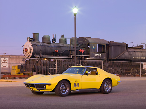 VET 03 RK0583 01 © Kimball Stock 1969 Chevrolet Corvette Coupe Yellow 3/4 Front View On Pavement By Train