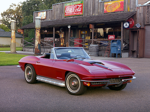 VET 03 RK0587 01 © Kimball Stock 1967 Chevrolet Corvette Sting Ray 427 Convertible Maroon 3/4 Front View On Pavement By Gas Station