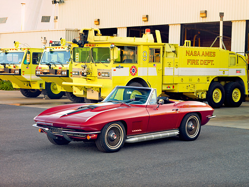 VET 03 RK0591 01 © Kimball Stock 1967 Chevrolet Corvette Sting Ray 427 Convertible Maroon 3/4 Front View On Pavement By Fire Trucks