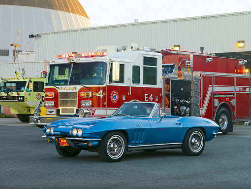 VET 03 RK0594 01 © Kimball Stock 1965 Chevrolet Corvette Convertible Nassau Blue 3/4 Front View On Pavement By Fire Trucks