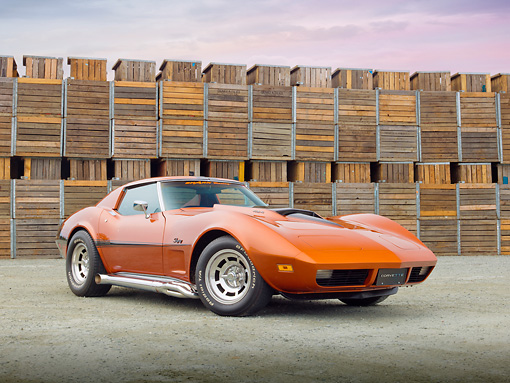 VET 05 RK0216 01 © Kimball Stock 1974 Chevrolet Corvette Sunburst Yellow 3/4 Front View On Gravel By Wooden Crates