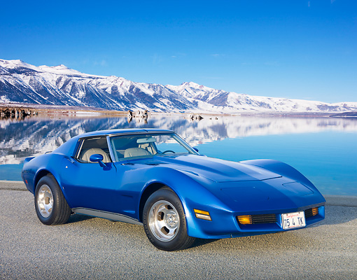 VET 05 RK0228 01 © Kimball Stock 1975 Chevrolet Corvette Blue 3/4 Front View On Pavement By Snowy Peaks And Water