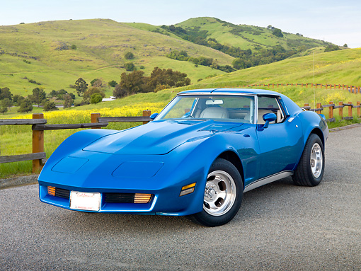 VET 05 RK0229 01 © Kimball Stock 1975 Chevrolet Corvette Blue 3/4 Front View On Pavement By Fence And Grassy Hills