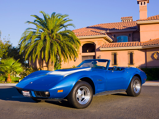 VET 05 RK0153 01 © Kimball Stock 1974 Chevrolet Corvette Convertible Blue 3/4 Front View On Pavement By Palm Tree Building Blue Sky
