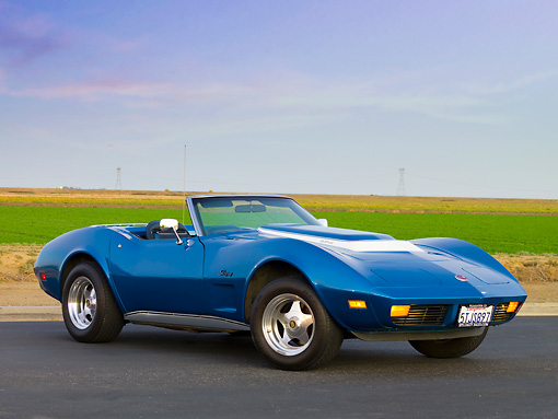 VET 05 RK0155 01 © Kimball Stock 1974 Chevrolet Corvette Convertible Blue 3/4 Front View On Pavement By Field And Blue Sky