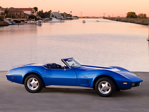 VET 05 RK0156 01 © Kimball Stock 1974 Chevrolet Corvette Convertible Blue 3/4 Front View On Pavement By Canal And Homes