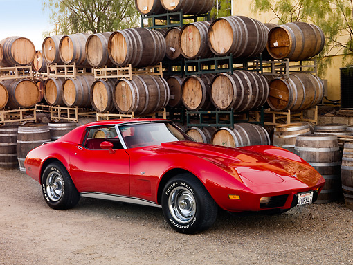 VET 05 RK0158 01 © Kimball Stock 1977 Chevrolet Corvette Coupe Red 3/4 Front View On Gravel By Wine Barrels