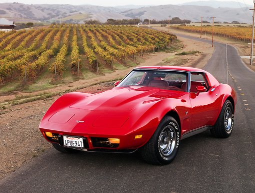 VET 05 RK0161 01 © Kimball Stock 1977 Chevrolet Corvette Coupe Red 3/4 Front View On Pavement By Vineyard