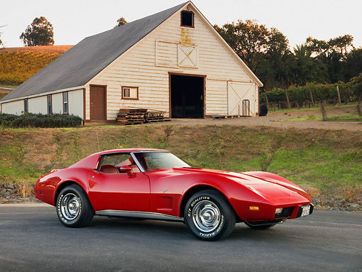 VET 05 RK0162 01 © Kimball Stock 1977 Chevrolet Corvette Coupe Red 3/4 Front View On Pavement By Barn