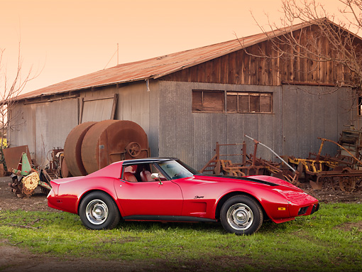 VET 05 RK0210 01 © Kimball Stock 1976 Chevrolet Corvette Stingray Red And Black Profile View By Barn