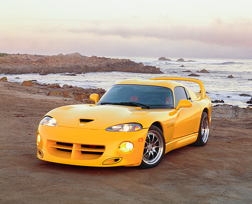 VIP 01 RK0150 03 © Kimball Stock 1996 Dodge Hennessey Viper Venom 650R Yellow 3/4 Front View On Sand By Rocks And Ocean Headlights On At Dusk