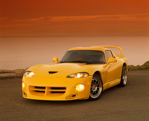 VIP 01 RK0131 01 © Kimball Stock 1996 Dodge Hennessey Viper Venom 650R Yellow 3/4 View On Pavement By Water At Dusk
