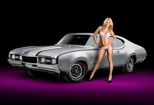 WMN 03 RK0307 01 © Kimball Stock 1968 Oldsmobile Hurst/Olds Silver With Black Stripes 3/4 Front View In Studio With Swimsuit Model