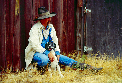 WRG 02 RK0071 02 © Kimball Stock Wrangler Leaning Against Barn Petting Dog